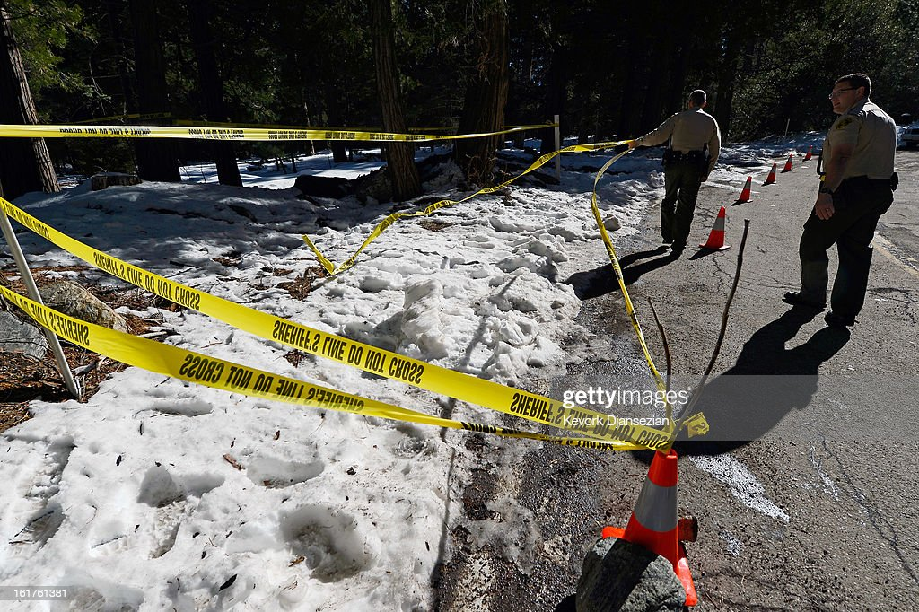 San Bernardino County Sheriff's deputy Alex Cundieff (R) and Chris Kelley secure the scene where a P22 Walther Suppressor hand gun was found in the snow just off Glass Road near where former Los Angeles Police Department officer Christopher Dorner crashed a purple Nissan truck, before carjacking a second truck as he was fleeing from law enforcement on February 15, 2013 in Big Bear, California. The gun was spotted February 15, by a local citizen. Dorner barricaded himself in a cabin near Big Bear, California, and engaged law enforcement officers in shootout, shooting two police, killing one and wounding the other. Dorner, a former Los Angeles Police Department officer and Navy Reserve veteran, who's body was identified in the burned cabin, was wanted in connection with the deaths of an Irvine couple and a Riverside police officer.