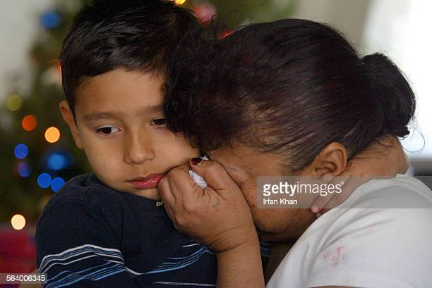 San Bernardino Dec12 2004 – – Aurelio Carrillo embraces and comforts grandmother Laurie Rey as the pair anticipates Christmas morning without his...