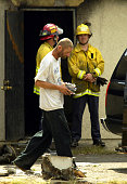 San Bernardino July 28 2003 –– Robert Henderson removes his belonging from after a early Monday morning blaze which gutted his house killing six...