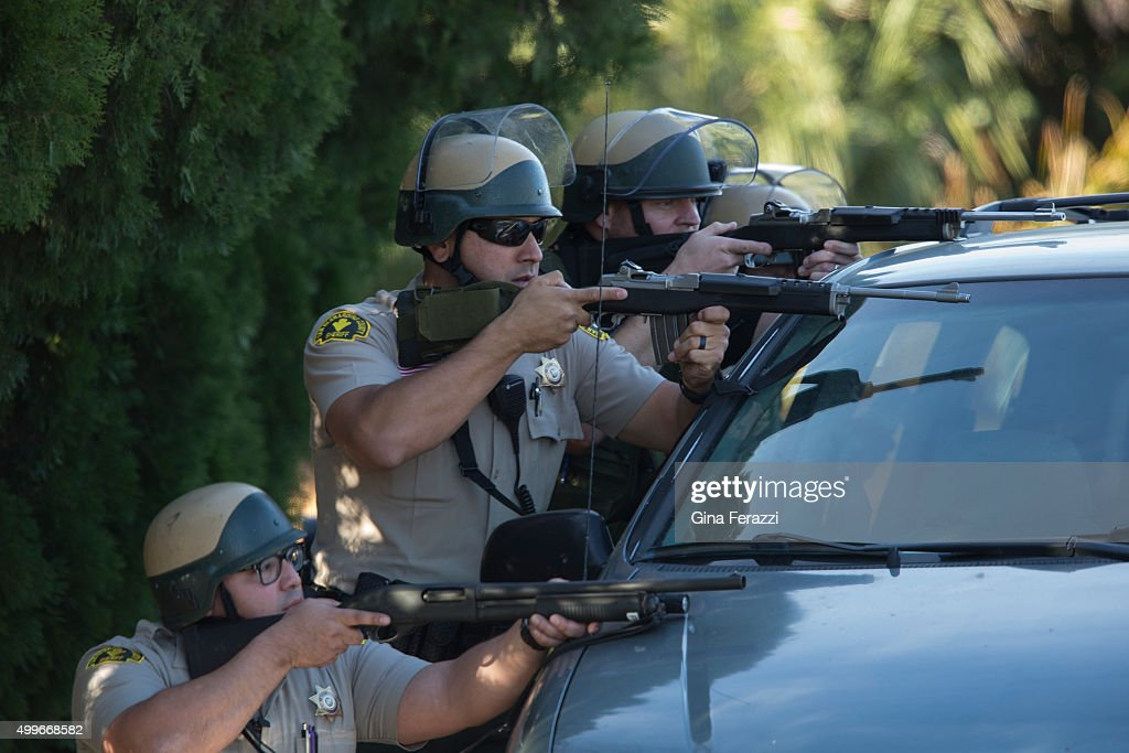 San Bernardino Sheriff Deputies draw guns and crouch behind a minivan on Richardson Street during an active search for the suspects involved in the...