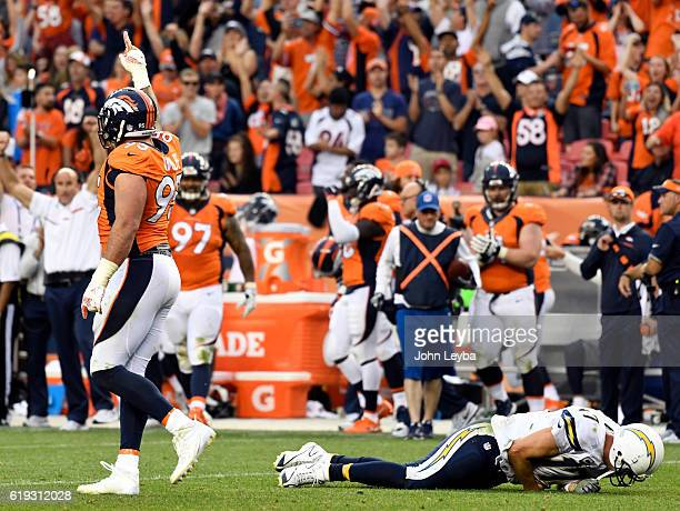 San Diego Chargers quarterback Philip Rivers lays on the ground after getting hit by Denver Broncos defensive end Derek Wolfe as he holds up his...