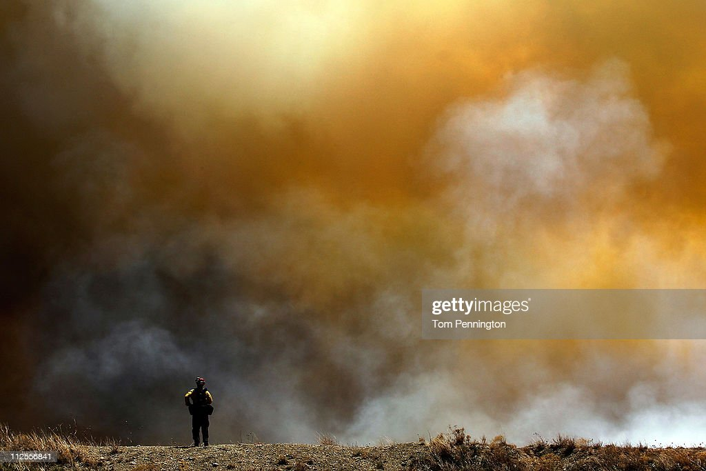 San Diego County firefighter Jason Lambirth surveys a running wildfire on April 19, 2011 in Strawn, Texas. Dozens of area homes have been destroyed in the wildfires that have been fueled by dry conditions, high winds, and low humidity.
