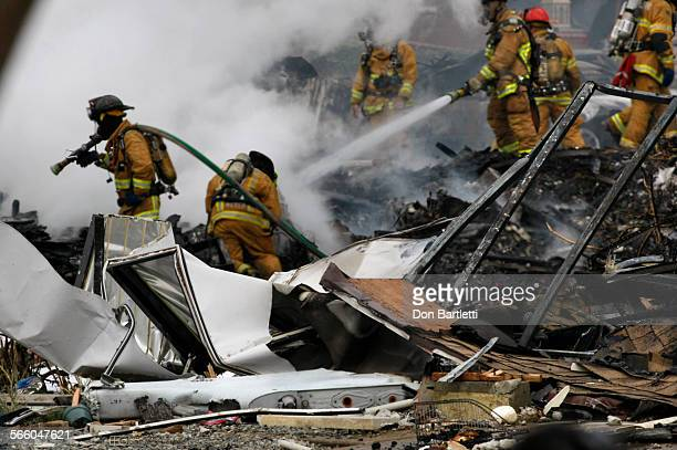 SAN DIEGO CA DECEMBER 8 2008 San Diego firefighters pour water on the wreckage of an F–18 mililtary jet that killed three people when it crashed into...