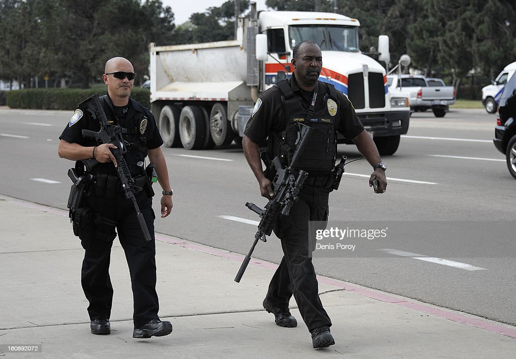 San Diego Harbor Police officers walk outside of Naval Base Point Loma as police search for suspect, former LAPD officer Christopher Jordan Dorner, February 7, 2013 in San Diego, California. A manhunt is underway for Dorner, who is suspected of shooting at police officers in the Southern California area.