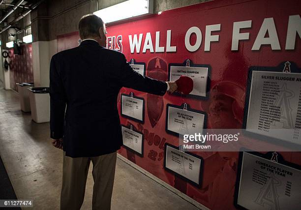 San Diego Padres broadcaster Dick Enberg touches the name of Alex Johnson of the California Angels on the team wall of fame before the game between...