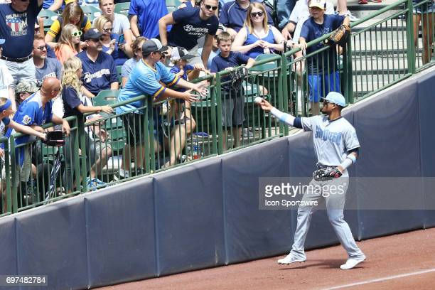 San Diego Padres left fielder Allen Cordoba hands a ball to a fan during a game between the Milwaukee Brewers and the San Diego Padres on June 18th...