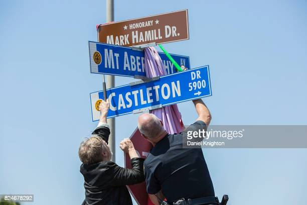 San Diego Police officer armed with a toy light saber aids actor Mark Hamill in unveiling a street sign dedicated in his honor on July 30 2017 in San...