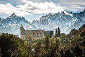 Ruin of San Francesco convent in the village of Castifao in Corsica set against snow covered mountains