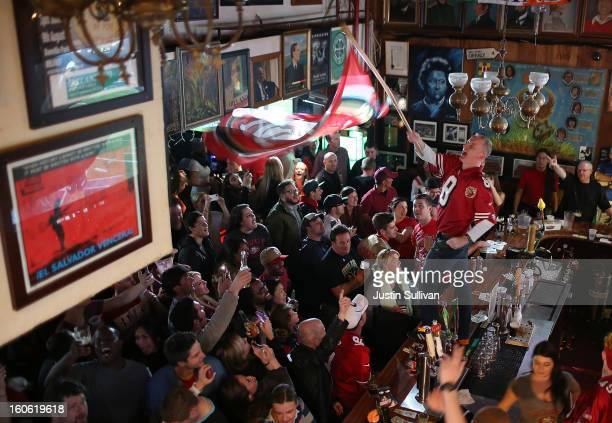 San Francisco 49er fan waves a flag on the bar at Ireland's 32 during a Super Bowl XLVII watch party on February 3 2013 in San Francisco California...