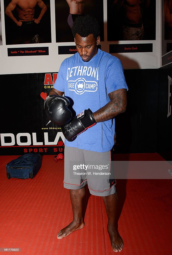 San Francisco 49ers defensive end Aldon Smith puts on a pair of boxing gloves before he starts working out with UFC Heavyweight fighter Daniel Cormier at AKA San Jose on February 15, 2013 in San Jose, California.
