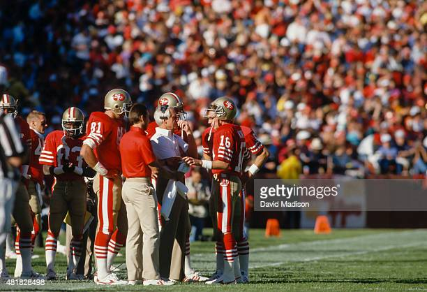 San Francisco 49ers Head Coach Bill Walsh confers on the sidelines with quarterback Joe Montana during an NFL football game against the St Louis...
