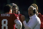 San Francisco 49ers head coach Bill Walsh talks to quarterback Joe Montana and backup quarterback Steve Young all members of the Pro Football Hall of...