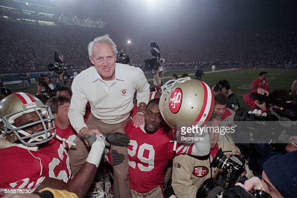 San Francisco 49ers players carry their coach Bill Walsh off the field after they win the 1985 Super Bowl