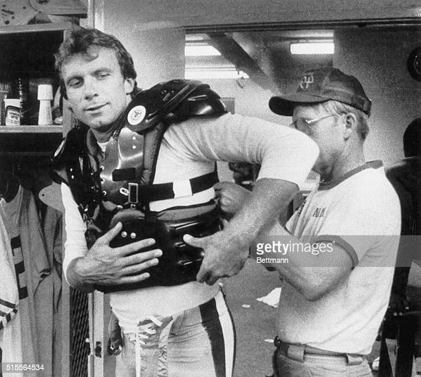 San Francisco 49ers' quarterback Joe Montana is helped on with his newlydesigned flakjacket to protect his injured ribs Montana sustained rib...