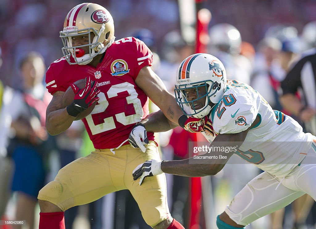 San Francisco 49ers running back LaMichael James (23) makes a first down during the second quarter as he is pushed out of bounds by Miami Dolphins free safety Reshad Jones (20) at Candlestick Park in San Francisco, California, on Sunday, December 9, 2012. The San Francisco 49ers defeated the Miami Dolphins, 27-13.
