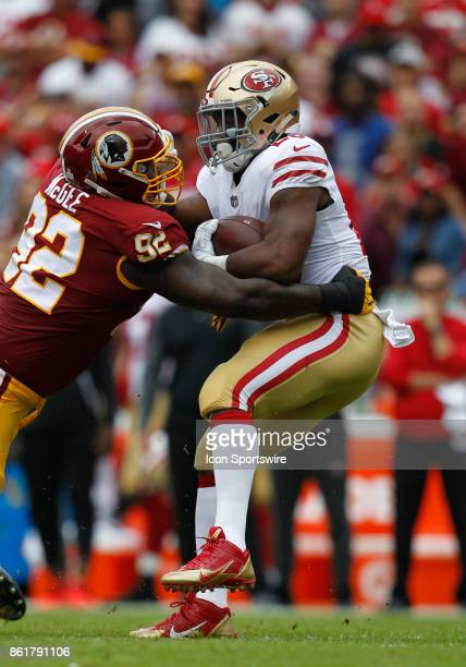 San Francisco 49ers runningback Carlos Hyde is hit and tackled by Washington Redskins defensive end Stacy McGee during a football game between the...