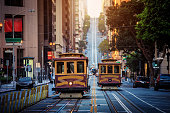 Classic view of historic traditional Cable Cars riding on famous California Street in beautiful early morning light at sunrise in summer with retro vintage style cross processing filter effect, San Fr