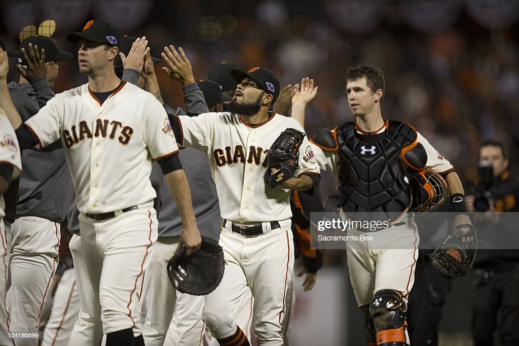 San Francisco Giants' Brandon Belt, Sergio Romo and Buster Posey exchange high fives after winning Game 2 of the National League Championship Series on Monday, October 15, 2012, at AT&T Park in San Francisco, California. The Giants won, 7-1.