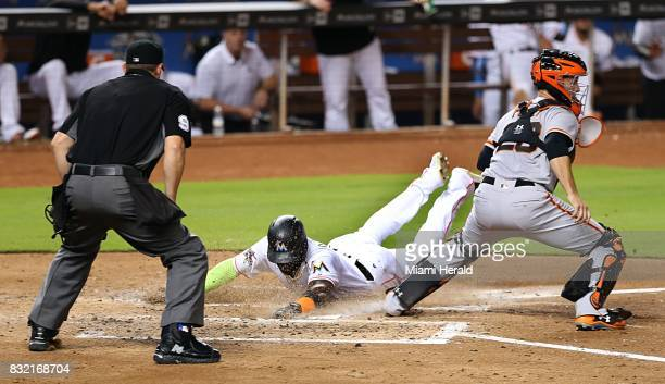 San Francisco Giants catcher Buster Posey right waits for a throw as the Miami Marlins' Marcell Ozuna slides safely at home plate after a sacrifice...