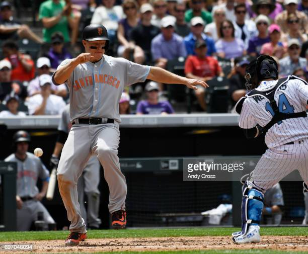 San Francisco Giants catcher Nick Hundley beats a throw in and tag for a run scored at the plate against Colorado Rockies catcher Tony Wolters in the...