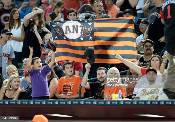 San Francisco Giants fans hold up a flag behind the visitor's dugout during the MLB baseball game between the San Francisco Giants and the Arizona...
