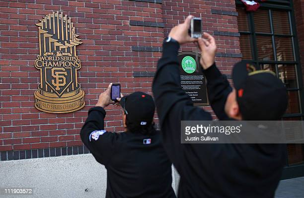 San Francisco Giants fans use their cell phones to take pictures of a World Series plaque before the start of the San Francisco Giants home opener...