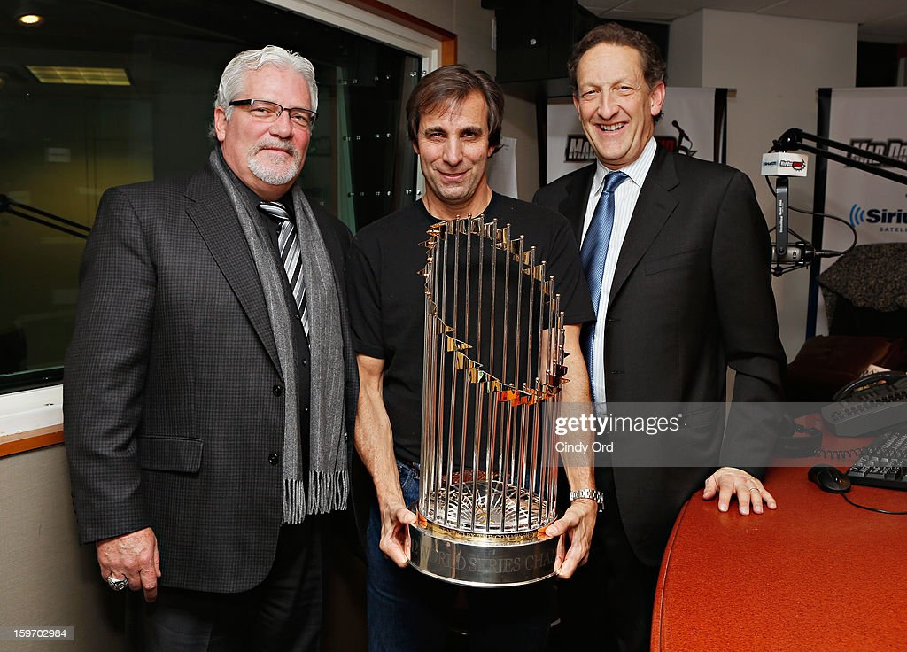San Francisco Giants general manager Brian Sabean (L) and San Francisco Giants CEO Larry Baer(R) pose with SiriusXM host Chris 'Mad Dog' Russo (C) as he holds the 2012 World Series trophy at the SiriusXM Studios on January 18, 2013 in New York City.
