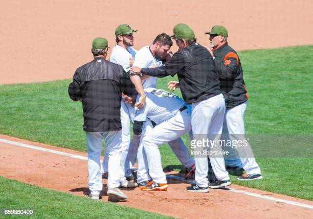 San Francisco Giants relief pitcher Hunter Strickland has to be restrained after a fight with Washington Nationals right fielder Bryce Harper during...