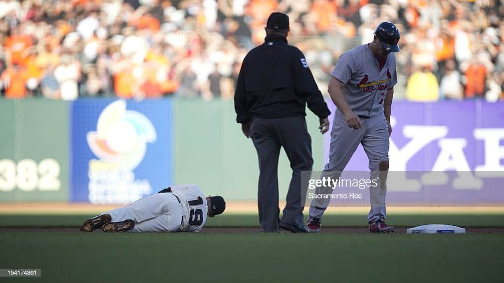 San Francisco Giants second baseman Marco Scutaro (19) lies on the infield after being knocked down by St. Louis Cardinals left fielder Matt Holliday (7) during Game 2 of the National League Championship Series on Monday, October 15, 2012, at AT&T Park in San Francisco, California.