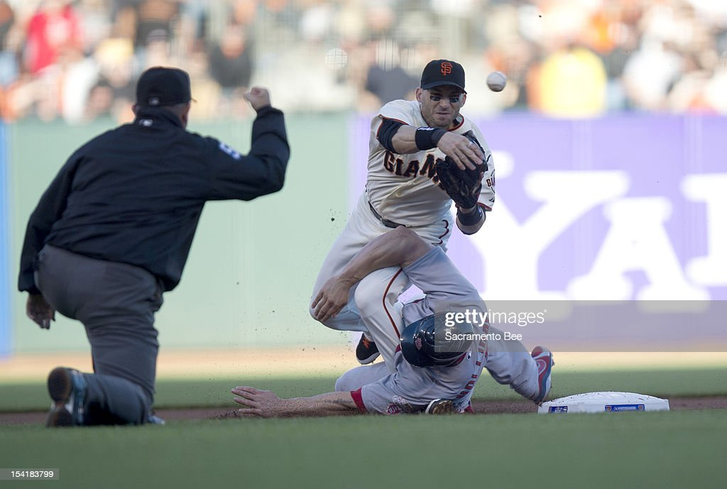 San Francisco Giants second baseman Marco Scutaro (19) throws to first as he's taken out by St. Louis Cardinals left fielder Matt Holliday (7) during Game 2 of the National League Championship Series on Monday, October 15, 2012, at AT&T Park in San Francisco, California.