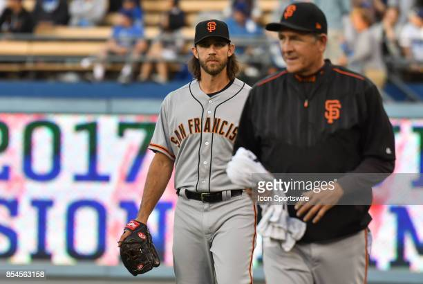 San Francisco Giants starting pitcher Madison Bumgarner walks in from the bullpen with pitching coach Dave Righetti during an MLB game between the...