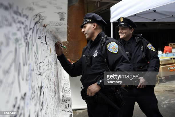 A San Francisco Police Department officer signs the final steel beam during a topping off ceremony for the Salesforce Tower in San Francisco...