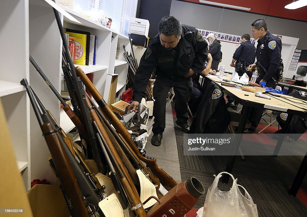 A San Francisco police officer adds a rifle to a stack of surrendered guns during a gun buy back program on December 15, 2012 in San Francisco, California. The San Francisco police department held a one-day gun buy back event that paid $200 per gun turned in. A better than expected crowd resulted in payback money running out and vouchers were issued to collect money within a week. Over 200 guns were collected.
