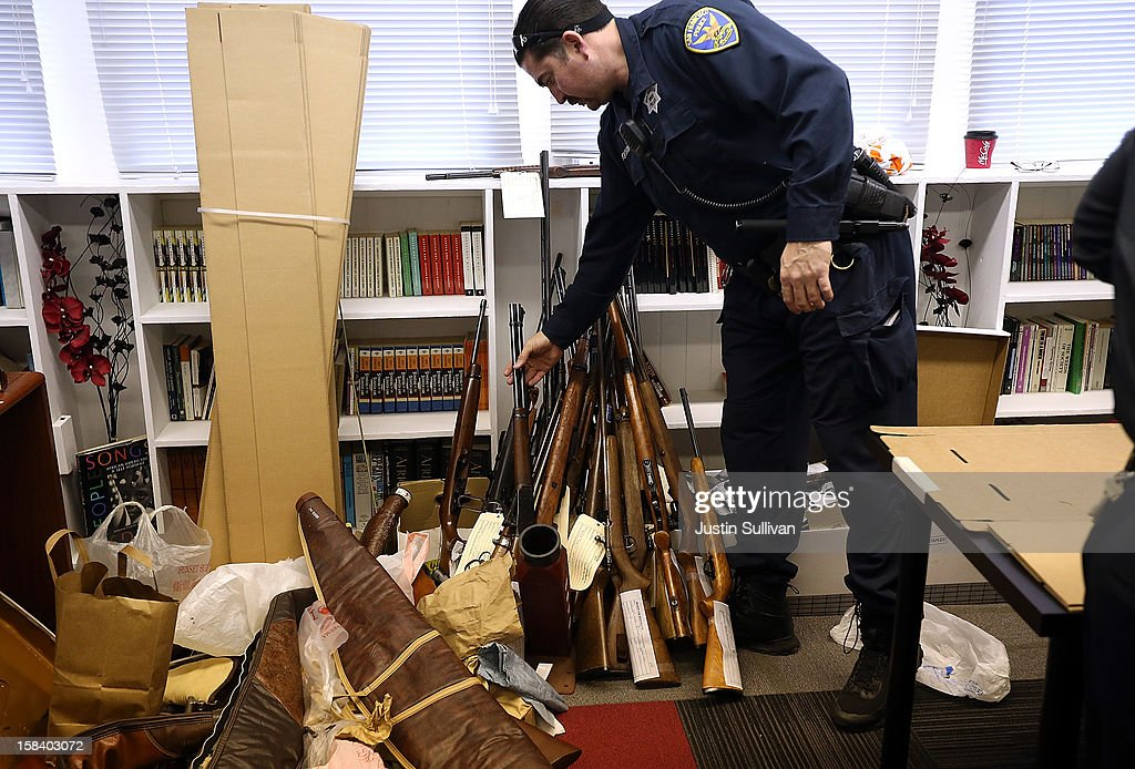 A San Francisco police officer adds a rifle to a stack of turned in guns during a gun buy back program on December 15, 2012 in San Francisco, California. The San Francisco police department held a one-day gun buy back event that paid $200 per gun turned in. A better than expected crowd resulted in payback money running out and vouchers were issued to collect money within a week. Over 200 guns were collected.