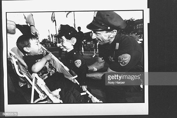 San Francisco police officer Bob Geary w his partner uniformed puppet cop Brendan O'Smarty chatting w giggling young boy in a stroller on street...