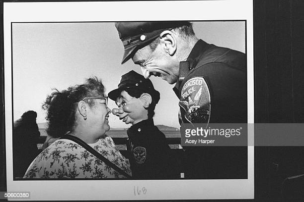 San Francisco police officer Bob Geary w his partner uniformed puppet cop Brendan O'Smarty chatting w amused woman on street during their patrol...