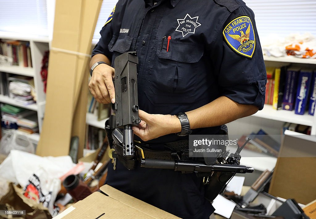 A San Francisco police officer inspects a gun that is being surrendered during a gun buy back program on December 15, 2012 in San Francisco, California. The San Francisco police department held a one-day gun buy back event that paid $200 per gun turned in. A better than expected crowd resulted in payback money running out and vouchers were issued to collect money within a week. Over 200 guns were collected.