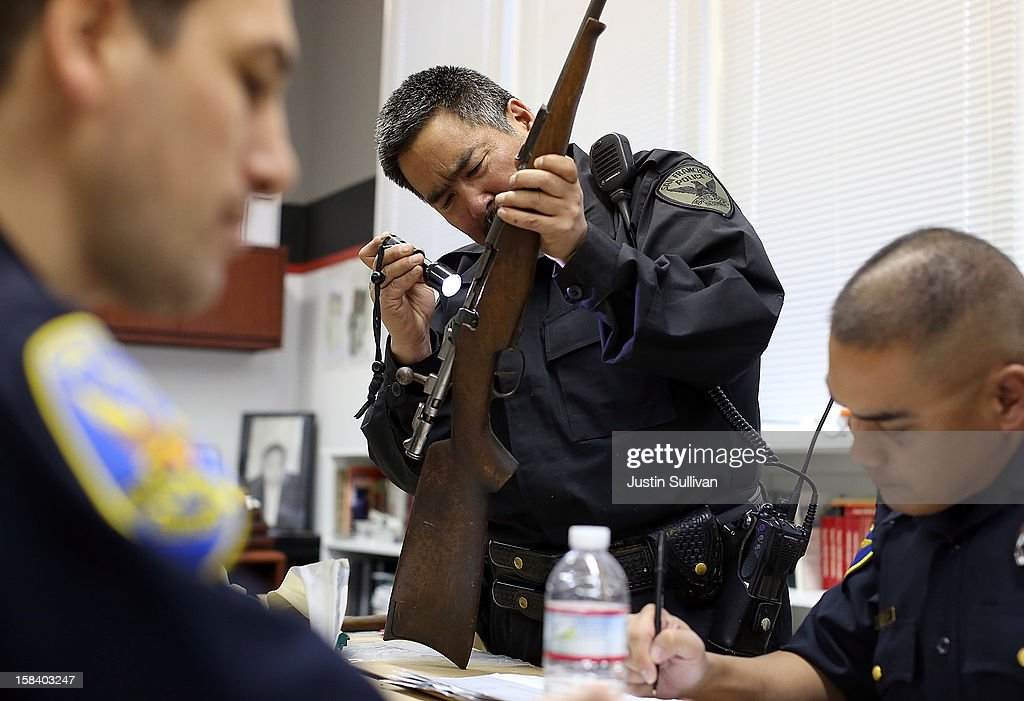 A San Francisco police officer inspects a rifle that is being surrendered during a gun buy back program on December 15, 2012 in San Francisco, California. The San Francisco police department held a one-day gun buy back event that paid $200 per gun turned in. A better than expected crowd resulted in payback money running out and vouchers were issued to collect money within a week. Over 200 guns were collected.