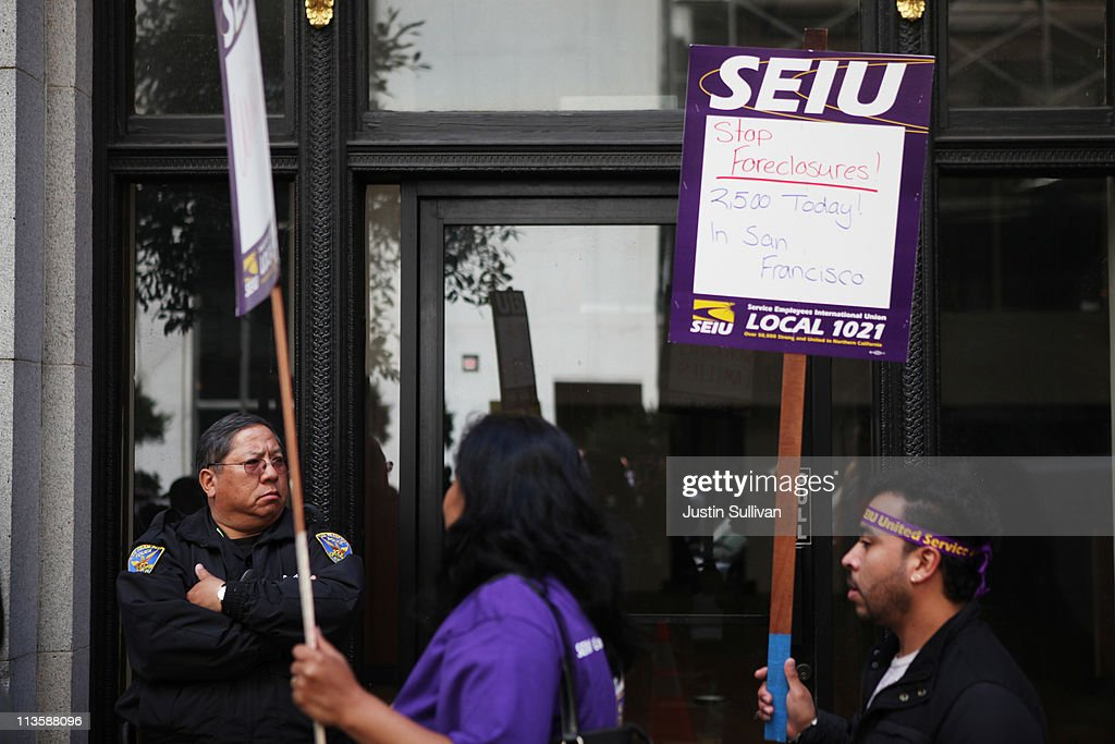 A San Francisco police officer monitors protestors as they hold signs during a demonstration outside of the Wells Fargo shareholders meeting on May 3, 2011 in San Francisco, California. Over 100 housing activists staged a demonstration outside of the Wells Fargo shareholders meeting accusing the banking giant of predatory lending, not paying taxes and foreclosing on homes by using fradulent paperwork.