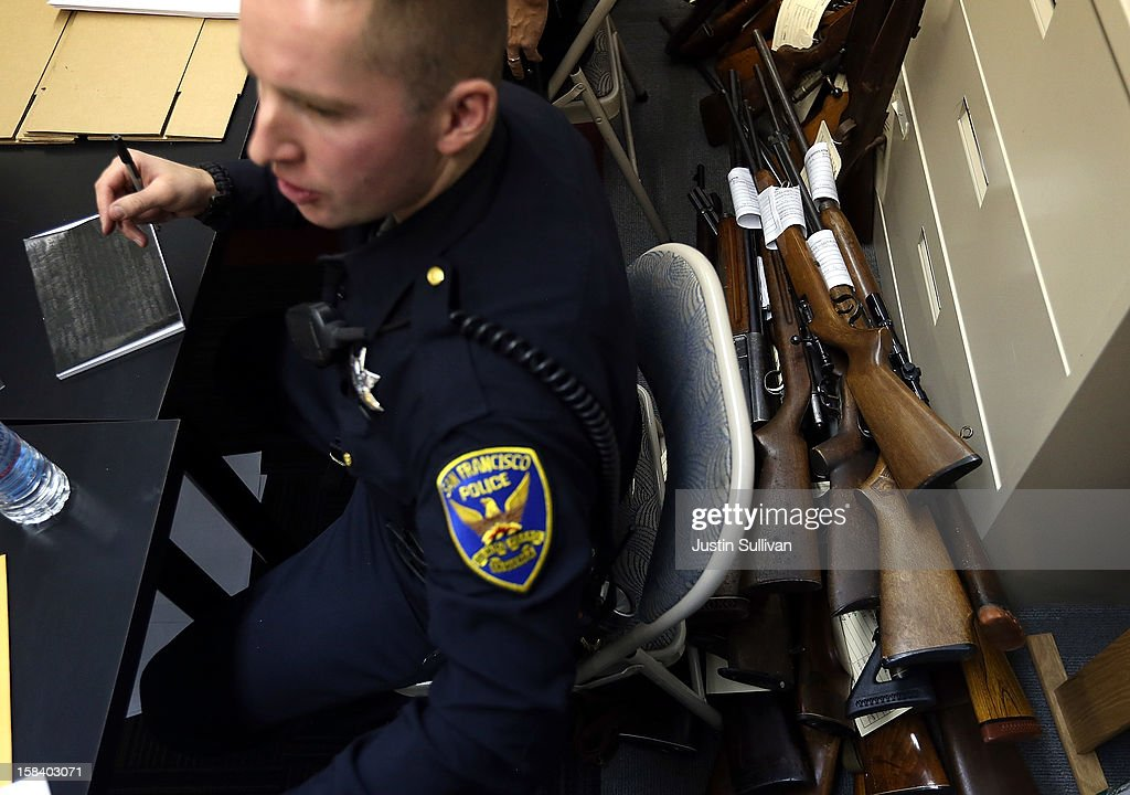 A San Francisco police officer sits next to a stack of rifles during a gun buy back program on December 15, 2012 in San Francisco, California. The San Francisco police department held a one-day gun buy back event that paid $200 per gun turned in. A better than expected crowd resulted in payback money running out and vouchers were issued to collect money within a week. Over 200 guns were collected.