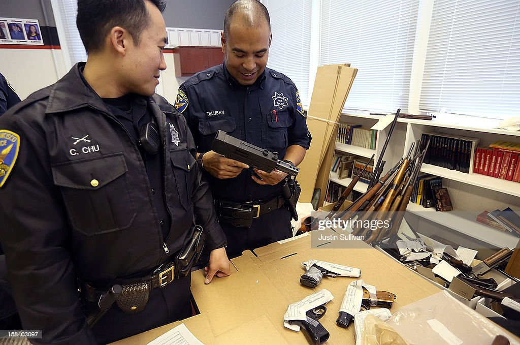 San Francisco police officers inspect a gun that was surrendered during a gun buy back program on December 15, 2012 in San Francisco, California. The San Francisco police department held a one-day gun buy back event that paid $200 per gun turned in. A better than expected crowd resulted in payback money running out and vouchers were issued to collect money within a week. Over 200 guns were collected.