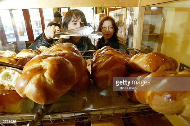San Francisco residents Jennifer Paul and Julie Wheeler shop for bread at the Arizmendi Bakery November 21 2003 in San Francisco California The...