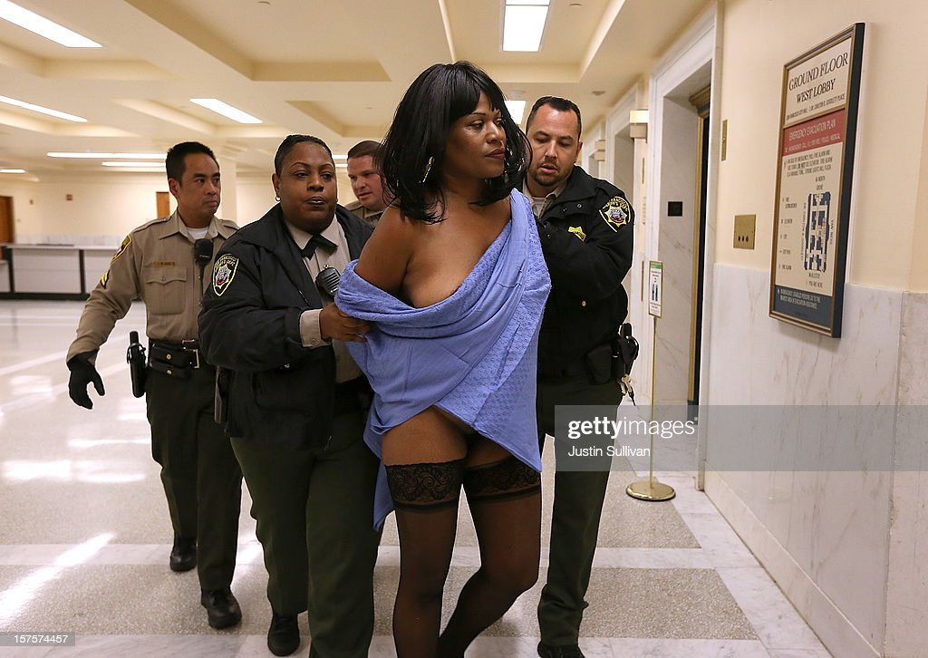 San Francisco Sheriff deputies detain a nude woman who stripped off her clothes during a San Francisco Board of Supervisors meeting on December 4, 2012 in San Francisco, California. The San Francisco Board of Supervisors voted to pass legislation that will amend the city's police code to ban nudity on city streets, plazas, sidewalks and other public spaces. Nudity during permitted parades, fairs and festivals will still be allowed.