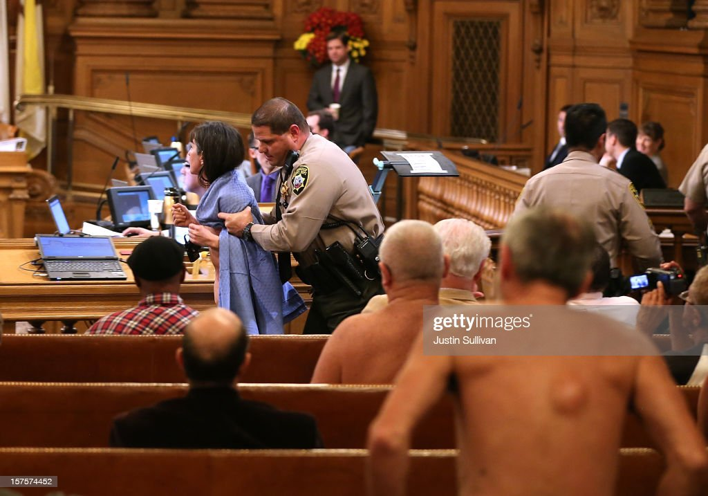 A San Francisco Sheriff deputy detains a nude woman who stripped off her clothes during a San Francisco Board of Supervisors meeting on December 4, 2012 in San Francisco, California. The San Francisco Board of Supervisors voted to pass legislation that will amend the city's police code to ban nudity on city streets, plazas, sidewalks and other public spaces. Nudity during permitted parades, fairs and festivals will still be allowed.