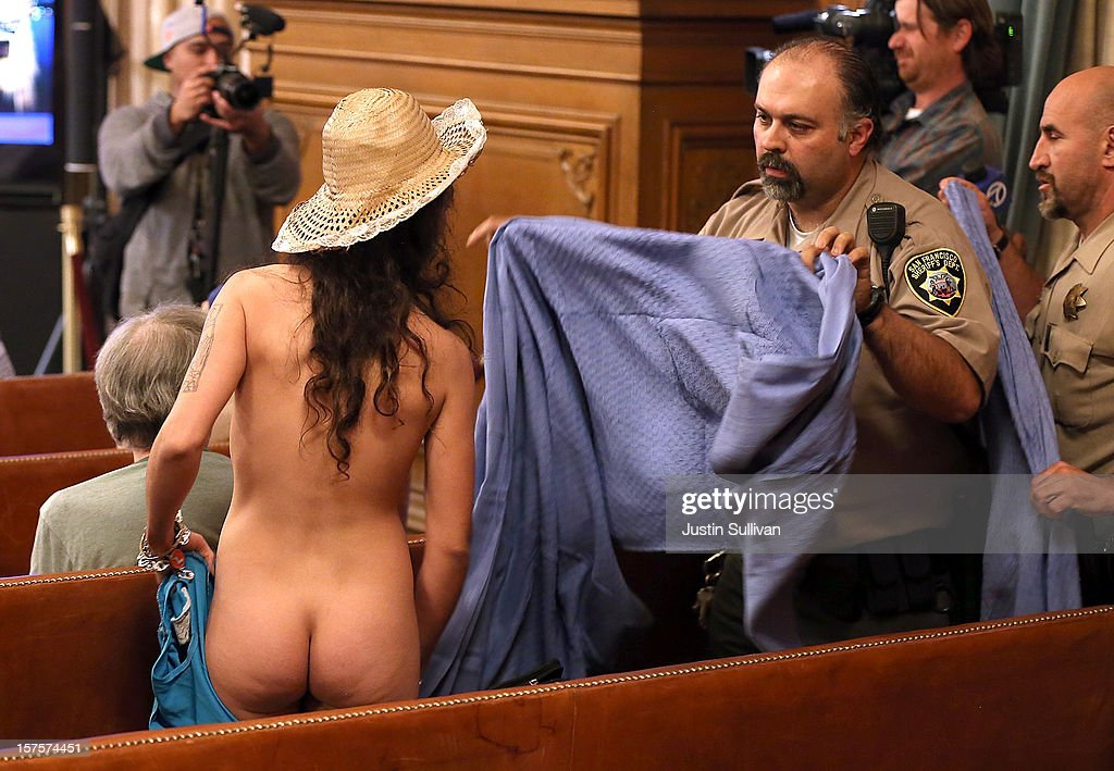 A San Francisco Sheriff deputy rushes to cover a nude woman who stripped off her clothes during a San Francisco Board of Supervisors meeting on December 4, 2012 in San Francisco, California. The San Francisco Board of Supervisors voted to pass legislation that will amend the city's police code to ban nudity on city streets, plazas, sidewalks and other public spaces. Nudity during permitted parades, fairs and festivals will still be allowed.