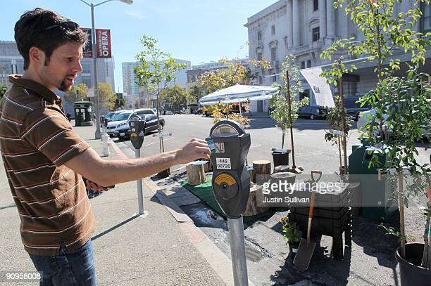 San Francisco unified School District director of sustainability Nik Kaestner feeds a parking meter for his display of trees and logs that takes up a...