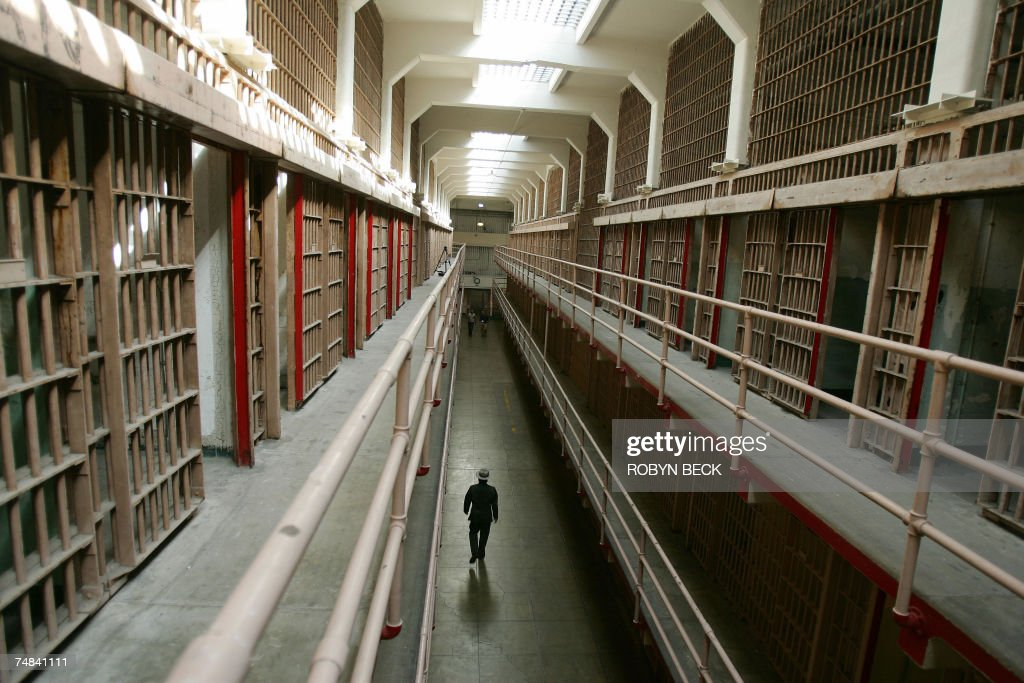 A National Park Service ranger walks down 'Broadway' in the main cell block on Alcatraz Island, 14 June 2007 in San Francisco Bay of California. Sometimes referred to as 'The Rock', the island of Alcatraz served first as a military fortification, before it became a federal penitentiary in 1934. Now Alcatraz is national recreation area under the supervision of the Naitonal Park Service (NPS) with more than a million visitors a year taking the short ferry ride from San Francisco's Fisherman's Wharf to experience the infamous maximum-security prison for high-risk convicts. Famous island residents have included 'Machine Gun' Kelly, Al Capone and Robert 'Birdman' Stroud. AFP PHOTO / Robyn BECK