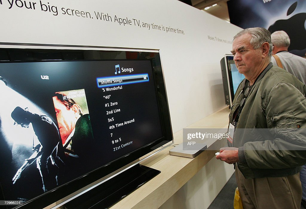 Phillip Belisle of San Francisco tries out Apple's new Apple TV at the Macworld Conference and Expo in San Francisco 10 January 2007. The set-top unit enables viewers to stream digitally downloaded video from a desktop or laptop computer to a television, complementing Apple's online film service which is available through its iTunes store. Apple TV comes equipped with a 40-gigabyte hard drive capable of storing up to 50 hours of video programming. It will be able to store videos, photos and music sent from computers within wireless range. The video box will be available in February and be priced at 299 USD. AFP PHOTO/Tony AVELAR