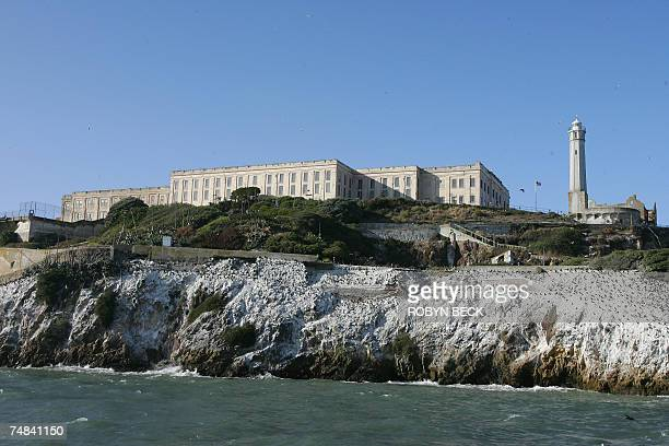 The main cell house is flanked by the lighthouse and the prision recreation yard and Alcatraz Island 14 June 2007 in San Francisco Bay of California...