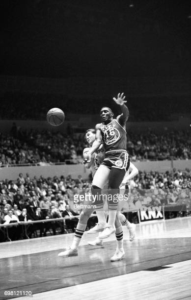San Francisco's Al Attles passes of to teammate Rudy LaRusso and blocks out Laker Jerry West in the same motion in first period action under the...